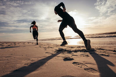 Couple exercising on the beach through jogging